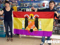 Propietarios de un bazar chino de Alicante mostrando bandera de España.